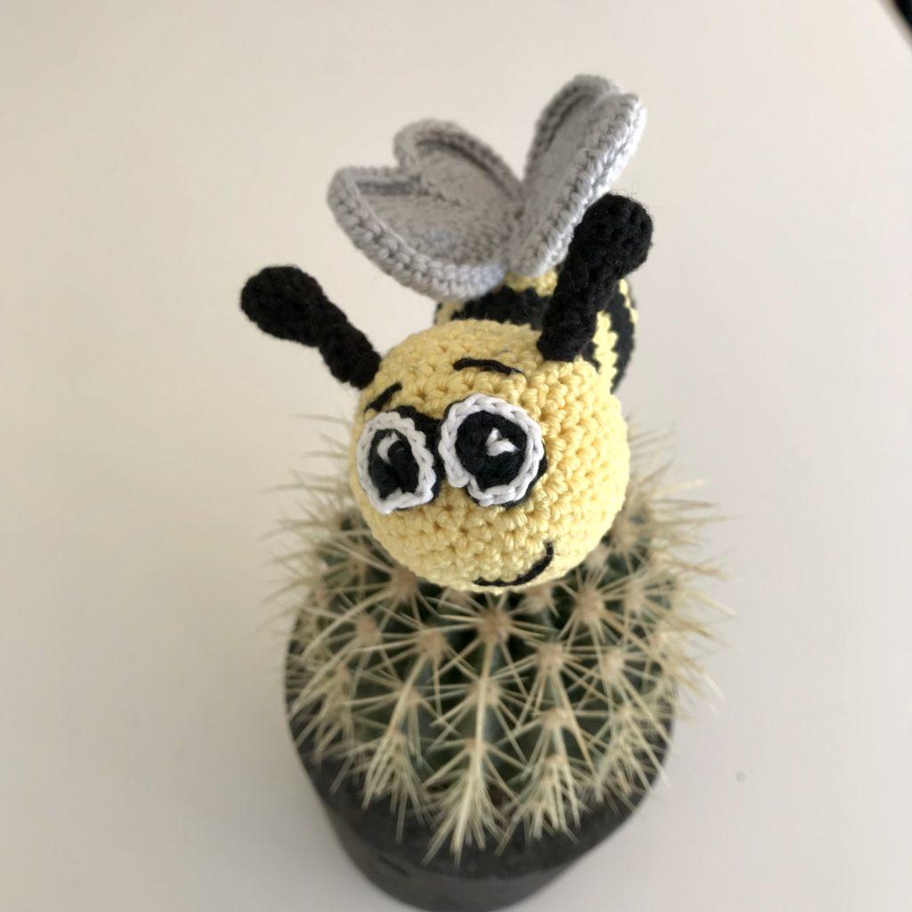Hæklet bi med grå vinger, sorte følehorn og hæklede øjne