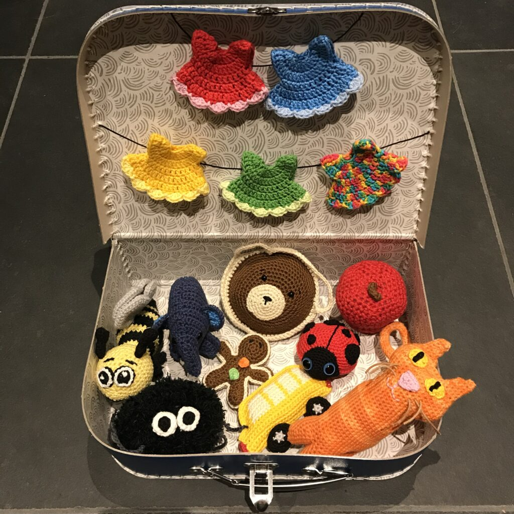 Hæklet sangkuffert med kjoler, dyr, chokolademand, bus og æble